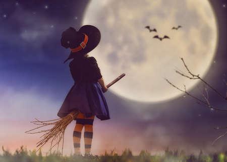 Feliz Halloween! pequeña bruja linda con un palo de escoba. chica hermoso del niño joven en traje de bruja al aire libre. Foto de archivo - 62765530