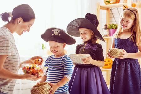幸せな家族は、ハロウィーンを祝う!若いお母さんは、お菓子で子供を扱います。カーニバルの衣装で面白い子供たち。