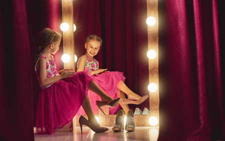 Cute little fashionista. Happy child girl try on outfits and mom's shoes looking at mirror. Stockfoto
