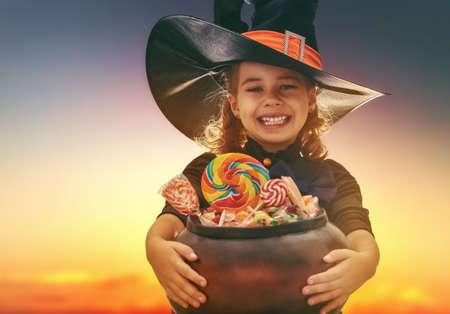 Feliz Dia das Bruxas! Bruxa pequena e linda com doces. Criança garota ao ar livre.