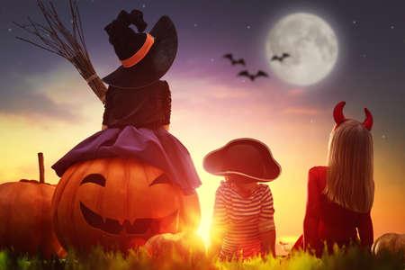 幸せな兄とハロウィーンの 2 人の姉妹。屋外のカーニバルの衣装で面白い子供たち。元気な子ども、夕日を背景にカボチャ。