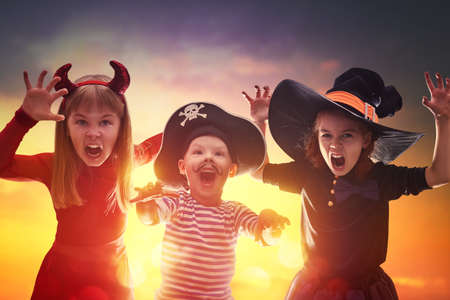 Happy brother and two sisters on Halloween. Funny kids in carnival costumes outdoors. Cheerful children on sunset background.