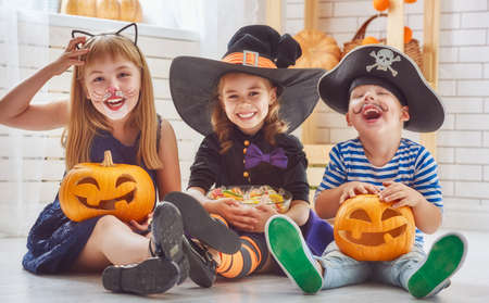 Happy brother and two sisters on Halloween. Funny kids in carnival costumes indoors. Cheerful children play with pumpkins and candy. Stok Fotoğraf