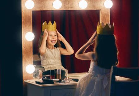 귀여운 여배우. 연극 장면과 거울의 배경에 공주 의상 자식 소녀.