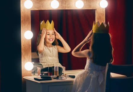 queen's theatre: Cute little actress. Child girl in Princess costume on the background of theatrical scenes and mirrors. Stock Photo