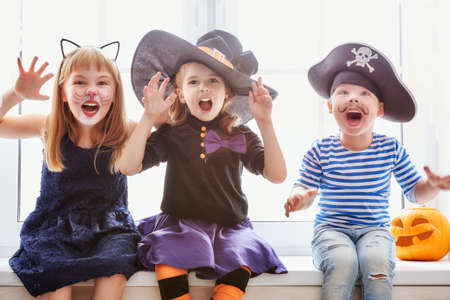 party hat: Happy brother and two sisters on Halloween. Funny kids in carnival costumes indoors. Cheerful children play sitting on the window.