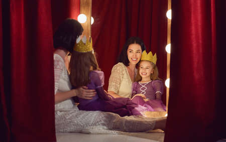 queen's theatre: Cute little actress. Young mother and her daughter child girl in Princess costume on the background of theatrical scenes and mirrors.