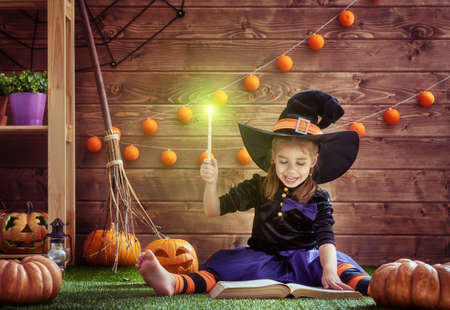 conjuring: Happy Halloween! Cute cheerful little witch with a magic wand and book of spells. Beautiful child girl in witch costume sitting on grass, conjuring and laughing. Stock Photo