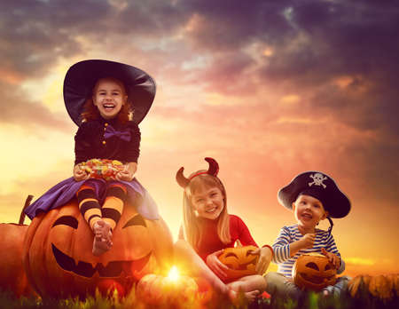 treat: Happy brother and two sisters on Halloween. Funny kids in carnival costumes outdoors. Cheerful children and pumpkins on sunset background.