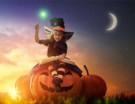 spells: Happy Halloween! Cute cheerful little witch with a magic wand and book of spells. Beautiful child girl in witch costume sitting on the big pumpkin, conjuring and laughing. Stock Photo