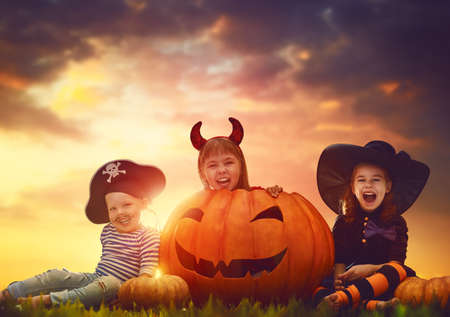 Happy brother and two sisters on Halloween. Funny kids in carnival costumes outdoors. Cheerful children and pumpkins on sunset background.