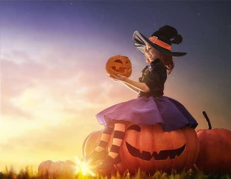 ¡Feliz Halloween! pequeña bruja linda con una calabaza grande. chica hermoso del niño joven en traje de bruja al aire libre.