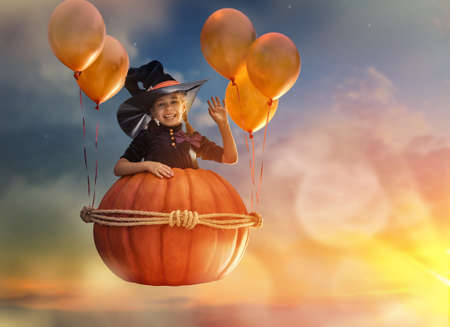 party hat: Happy Halloween! Cute little witch with a big pumpkin. Beautiful young child girl in witch costume outdoors.