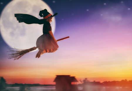 vestido de noche: ¡Feliz Halloween! pequeña bruja linda que vuela en una escoba. chica hermoso del niño joven en traje de bruja al aire libre.