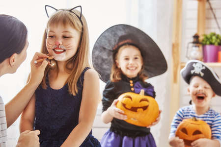 幸せな家族は、ハロウィーンを用意!若いママとカーニバルの衣装で彼女の子供たちは、休日を祝います。