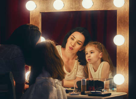 mirror: Happy loving family. Mother and daughter are doing makeup and having fun. Mother and daughter sitting at dressing table and looking at the mirror. Stock Photo