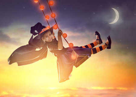 ¡Feliz Halloween! Pequeña bruja linda en el oscilación en la puesta del sol. chica hermoso del niño joven en traje de bruja al aire libre.