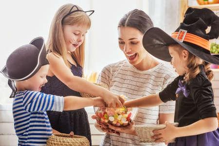 Happy family célébrer Halloween! Jeune maman traite les enfants avec des bonbons. enfants drôles en costumes de carnaval. Banque d'images - 62992089