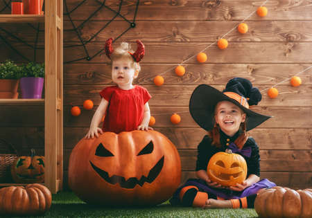 Two cute funny sisters celebrate the holiday. Jolly children in carnival costumes ready for Halloween. Stock Photo