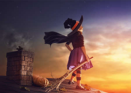 broomstick: Happy Halloween! Cute little witch with a broomstick. Beautiful young child girl in witch costume on the roof.