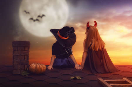 Two happy sisters on Halloween. Funny kids in carnival costumes sitting on the roof. Cheerful children looking at moon.