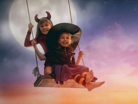 Two happy sisters on Halloween. Funny kids in carnival costumes outdoors. Cheerful children on swings on sunset background. Stock Photo