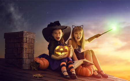 spells: Two happy sisters on Halloween. Funny kids in carnival costumes sitting on the roof. Cheerful children with pumpkin, magic wand and book of spells.
