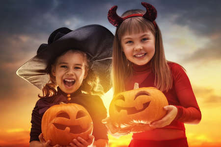 Two happy sisters on Halloween. Funny kids in carnival costumes outdoors. Cheerful children and pumpkins on sunset background. Standard-Bild