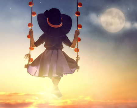 Happy Halloween! Cute little witch on swing in sunset. Beautiful young child girl in witch costume outdoors.