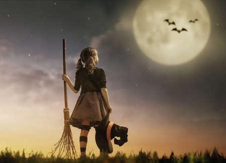 ¡Feliz Halloween! pequeña bruja linda con un palo de escoba. chica hermoso del niño joven en traje de bruja al aire libre.