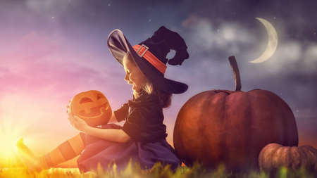 fruit orange: Happy Halloween! Cute little witch with a big pumpkin. Beautiful young child girl in witch costume outdoors.