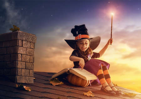 conjuring: Happy Halloween! Cute cheerful little witch with a magic wand and book of spells. Beautiful child girl in witch costume sitting on the roof, conjuring and laughing.