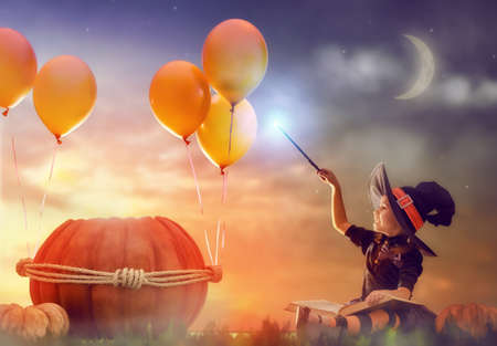 conjuring: Happy Halloween! Cute cheerful little witch with a magic wand and book of spells. Beautiful child girl in witch costume sitting near the big pumpkin, conjuring and laughing. Stock Photo