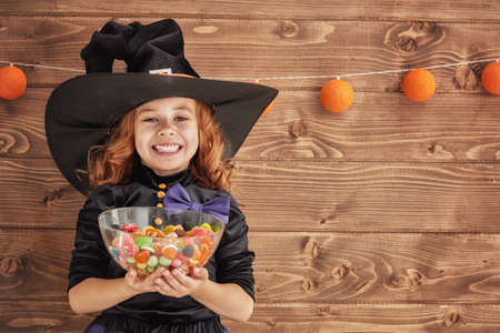 Happy Halloween! Cute little witch with candy.