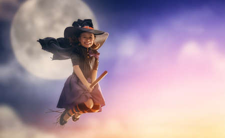 Happy Halloween! Cute little witch flying on a broomstick. Beautiful young child girl in witch costume outdoors.
