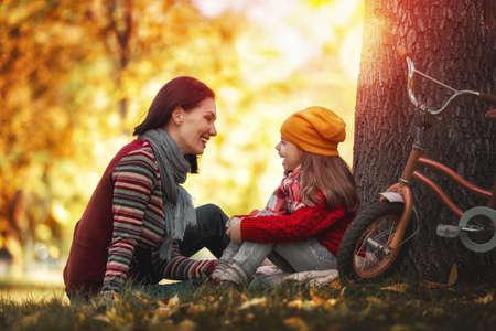 秋の散歩に幸せな家族!母と娘は公園を歩いて、美しい秋の自然を満喫します。 写真素材 - 64787861