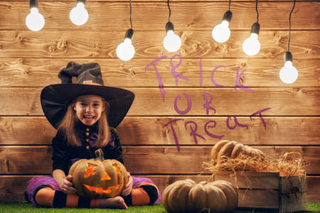 party hat: Happy Halloween! Cute little witch with a pumpkin.