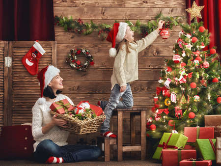 christmas time: Merry Christmas and Happy Holiday! Mom and daughter decorate the Christmas tree. Stock Photo