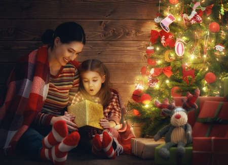 Merry Christmas and Happy Holiday! Loving family mother and child with magic gift box on Christmas. Stock Photo