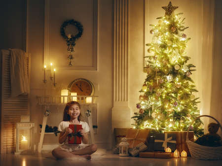 christmas present box: Merry Christmas and Happy Holiday! Cute little child girl with Christmas present. Kid holds a gift box.