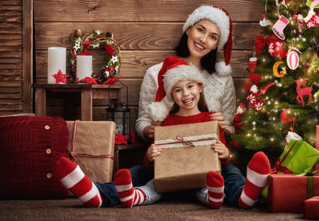 christmas spirit: Merry Christmas! Mother and her daughter child girl exchanging Christmas gifts Stock Photo