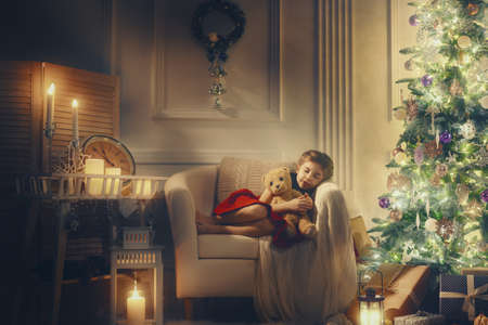 christmas light: Merry Christmas and Happy Holiday! Cute little child girl sleeping near Christmas tree.