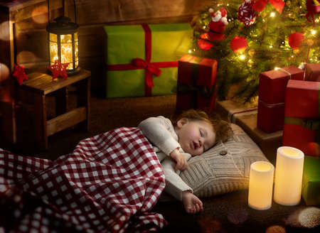 baby near christmas tree: Merry Christmas and Happy Holiday! Cute little child baby girl sleeping near Christmas tree. Stock Photo