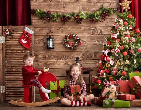 niñas jugando: Feliz Navidad y Feliz día de fiesta! Dos hermanas lindo muchachas de los niños que juegan juntos en Navidad.