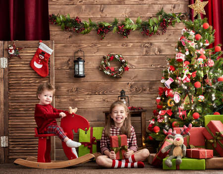 miracle tree: Merry Christmas and Happy Holiday! Two cute children sisters girls playing together on Christmas. Stock Photo