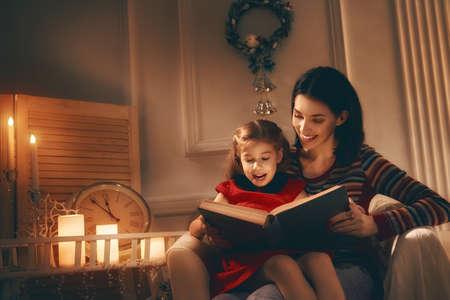 Buon Natale! Piuttosto giovane madre la lettura di un libro a sua figlia.