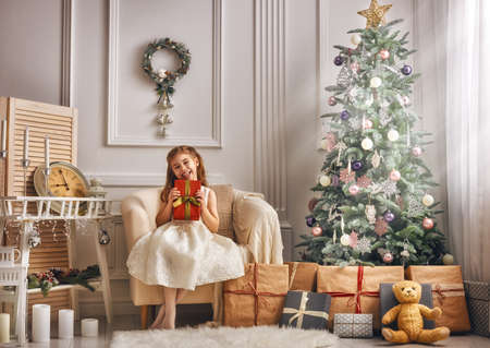 christmas present box: Merry Christmas and Happy Holidays! Cheerful cute little child girl with present. Kid holds a gift box near Christmas tree indoors.