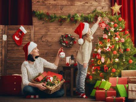 Prettige Kerstdagen en Happy Holidays! Moeder en dochter versieren van de kerstboom in de kamer. Liefdevolle familie binnenshuis.