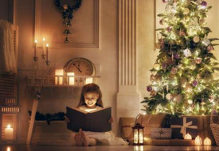 Feliz Navidad y felices fiestas! La niña alegre niño lindo con libro mágico. Del niño lee un cuento de hadas cerca del árbol de Navidad en el interior. Foto de archivo - 64939434