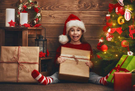christmas present box: Merry Christmas and Happy Holidays! Cheerful cute child girl with present. Kid holds a gift box near Christmas tree indoors.